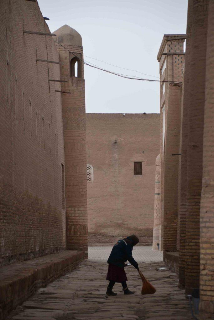Mujer barriendo la calle en Khiva