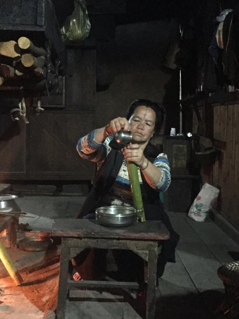Mujer de nuestro alojamiento preparando carne asada en bambú tradicional