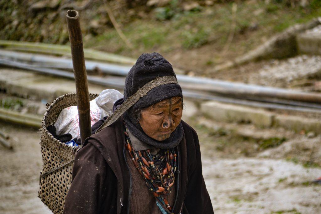 Mujer apatani anciana viniendo de trabajar