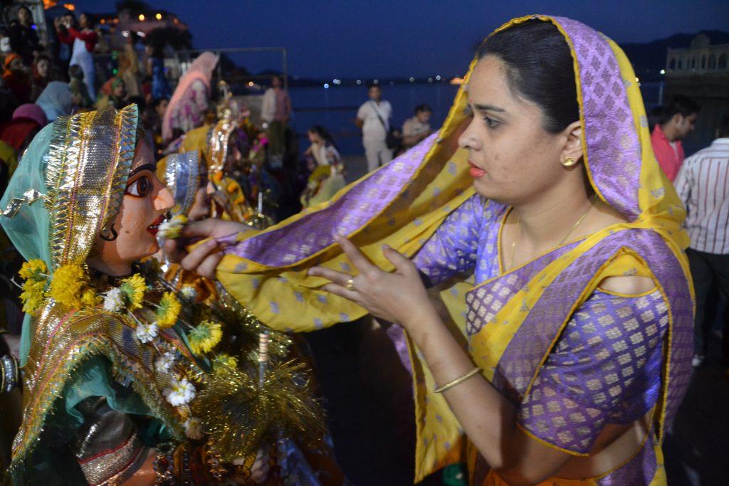 Al final de la procesión cada mujer deja su imagen de la diosa en la orilla del lago Pichola y le reza de rodillas pasándole una flor por su rostro