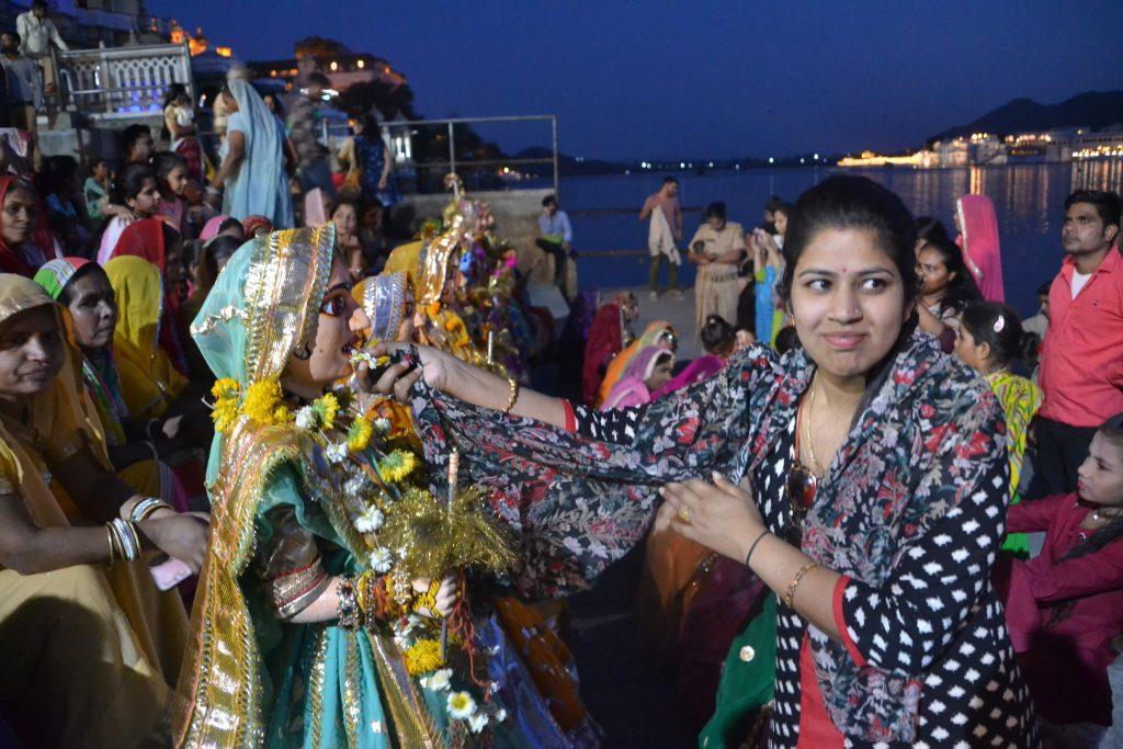 Mujer hindú adorando a la diosa a orillas del lago Pichola en Udaipur