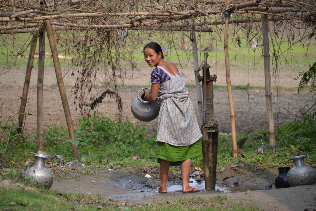 Mujer tribal llenando agua de la fuente