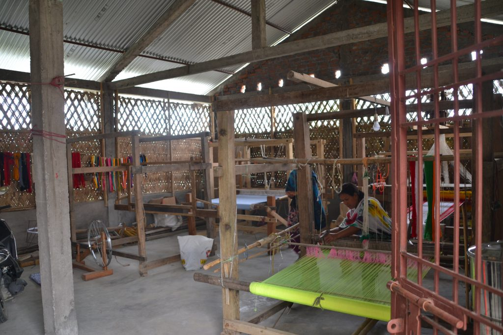 Mujeres de la cooperativa tejiendo con la máquina tradicional de Majuli