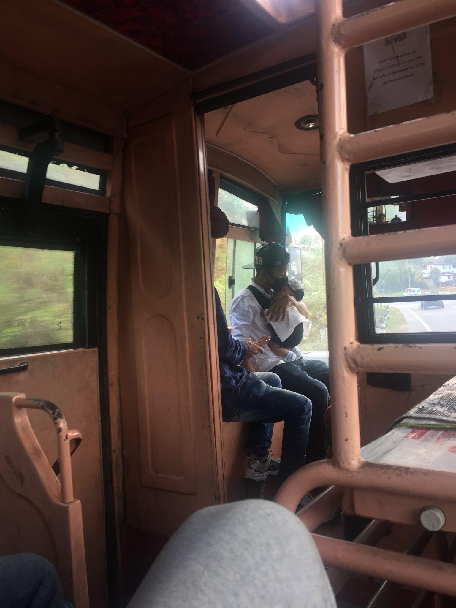 Hombre cuidando de su bebé en el autobús. La mamá está sentada charlando. Es muy normal esta imagen que choca con el resto de India